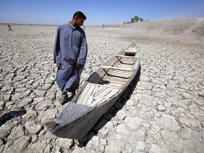 في هذه الصورة التي التقطت في يوم الجمعة 27 ايار 2009، يقف عبد الله بجوار قاربه في هور الحَمار الجاف في جنوب العراق. (AP)