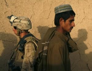 جندي مارينز أميركي من شركة ليما يمر بقرب رجل أفغاني خلال دورية في محافظة هيلماند – 8/4/2010 أسماء وجيه/ رويترز
