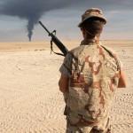 جندي أمريكي قرب الحدود الكويتية مع العراق وهو يشاهد سحابة من الدخان في الأفق، الكويت، كانون الثاني 1991، وكان جزئا من التحالف الذي تقوده الولايات المتحدة الذي طرد قوات صدام حسين من الكويت. صورة: بيتر تيرنلي\ كوربس