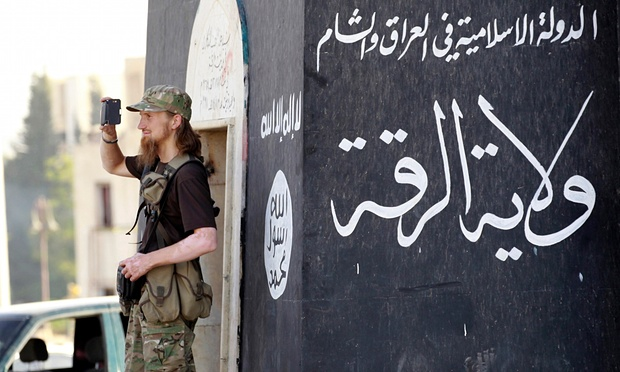 مقاتل يصور العرض العسكري لداعش في محافظة الرقة، سوريا. صورة: رويترز.