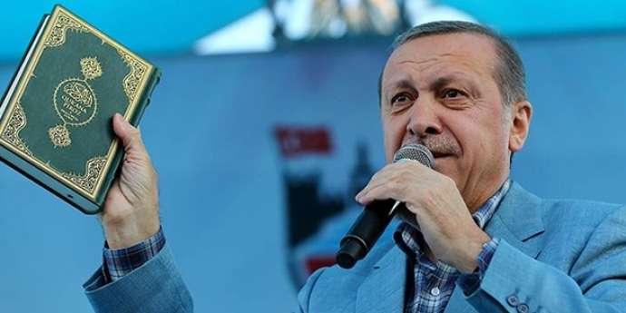 الرئيس التركي وهو يرفع نسخة من كتاب الله المجيد في حملة انتخابات تموز 2015