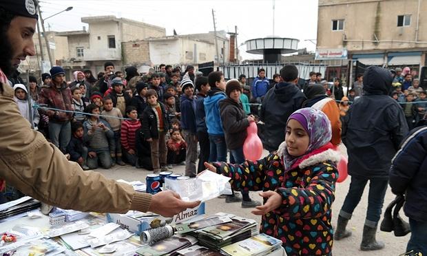مقاتل في داعش يوزع المشروبات الغازية، والبسكويت، والكتيبات الدينية للسكان المحليين في تل الأبيض، شمال سوريا. صورة: اوسشتيد برس.