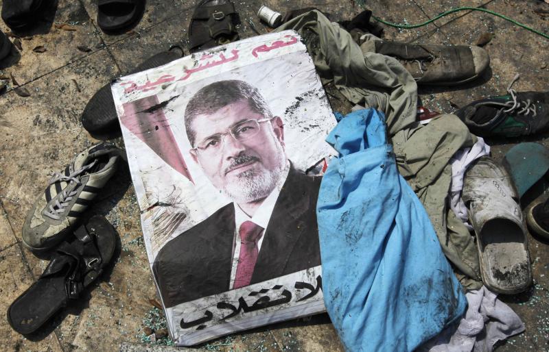 ملصق للرئيس المصري المخلوع محمد مرسي وسط حطام مخيم احتجاج مسح في القاهرة، أغسطس 2013. رويترز