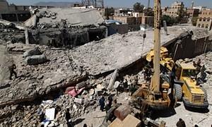 رجال الانقاذ اليمنيين يبحثون عن الضحايا تحت أنقاض مركز للشرطة وذلك بعد أن تم قصفه ليلا  في غارات جوية سعودية في 18  كانون الثاني في العاصمة اليمنية صنعاء و التي يسيطر عليها الحوثيون. تصوير محمد هويس