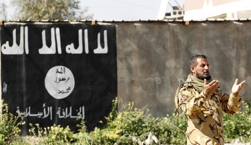 احد مقاتلي الحشد الشعبي وهو يصلي بجوار حائط رسم عليه علم أسود يستخدم من قبل مسلحي داعش في بلدة العلم، العراق، 10 أذار 2015. ثائر السوداني- رويترز