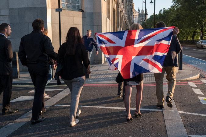أحد أنصار حملة مغادرة الإتحاد محاطة بعلم الممكلة المتحدة وسط العاصمة لندن يوم الجمعة . تصوير آدم فيرغسون لصحيفة نيويورك تايمز.