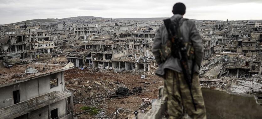 يقف موسى الشاب الكردي ذو 25 عاماً فوق مبنى يطل على بلدة كوباني السورية المدمرة. 30 كانون الثاني 2015. تصوير: غيتي إيماجيس.