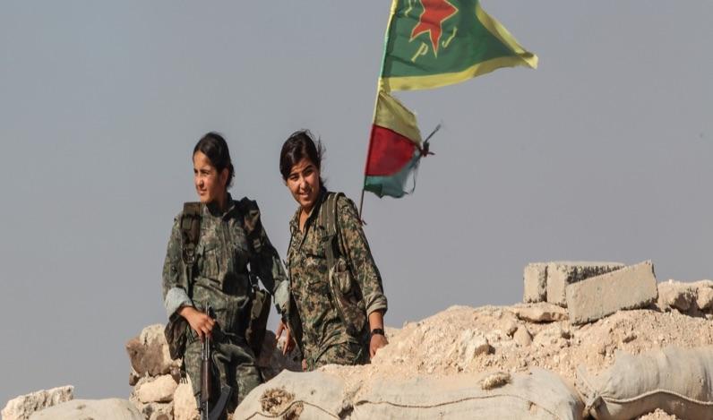مقاتلات في وحدات حماية الشعب تقفان بالقرب من نقطة تفتيش في ضواحي مدينة كوباني السورية المدمرة. تصوير: غيتي إيماجيس